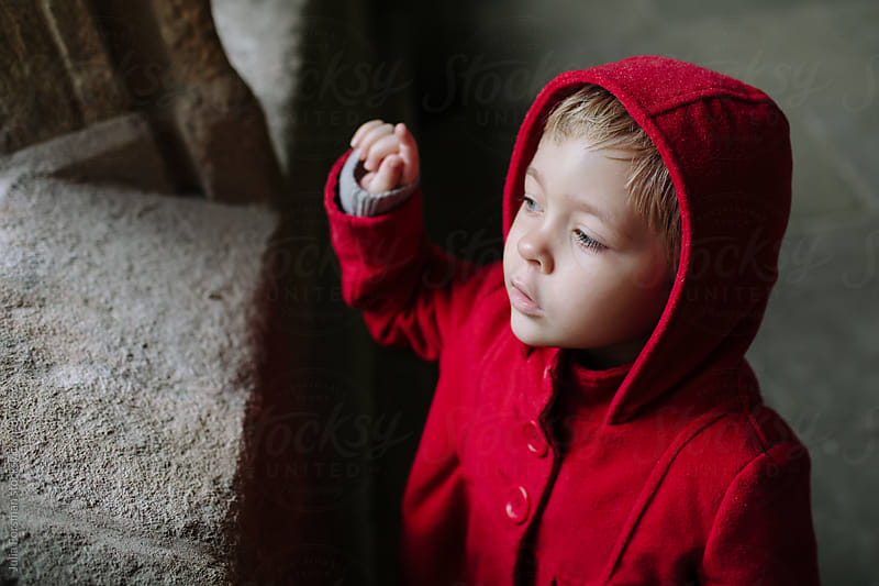 Little girl in red coat discussing what she is looking at (unseen). by Julia Forsman for Stocksy United