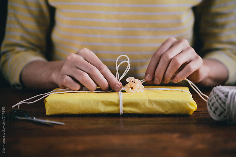 Hands gift wrapping a small present by Lior + Lone for Stocksy United