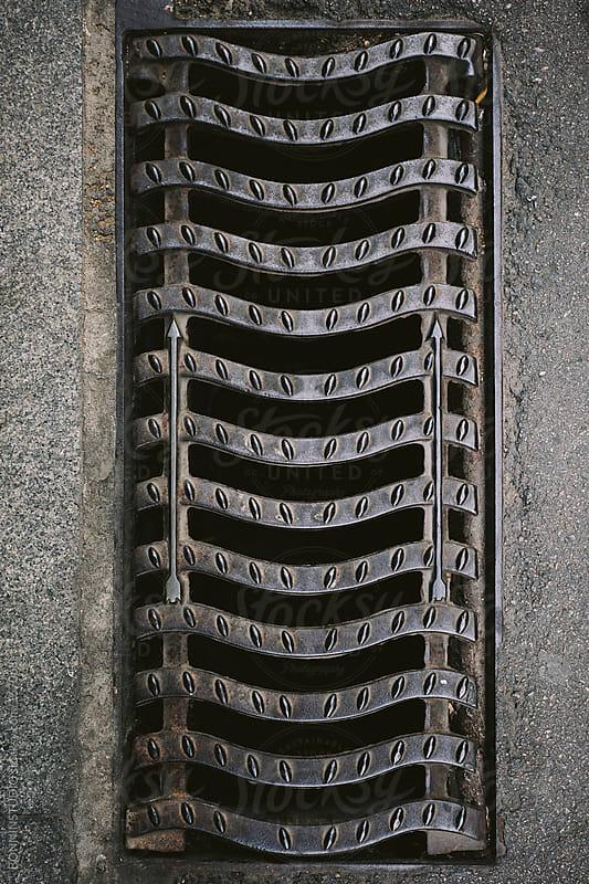 Arrows in  street sewer cap. by BONNINSTUDIO for Stocksy United