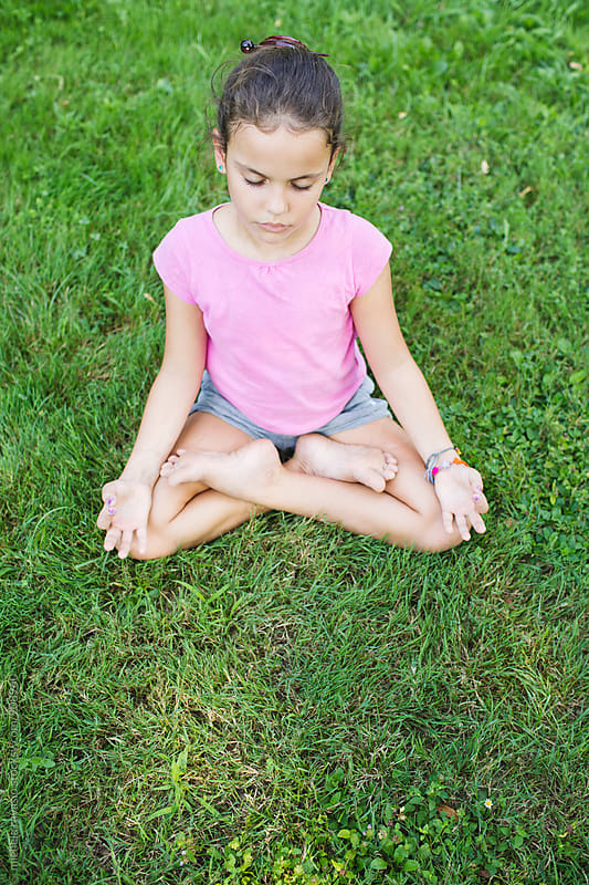 Little girl meditating outdoors by michela ravasio for Stocksy United