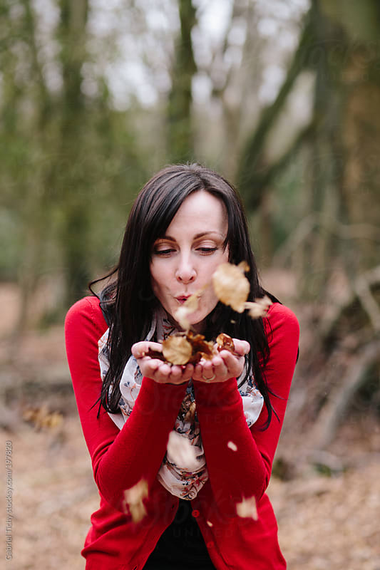 Young woman having fun with brown leaves by Gabriel Tichy for Stocksy United