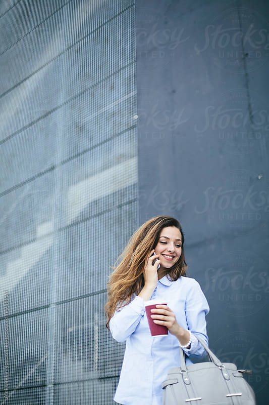 Young businesswoman using her smartphone by Aleksandar Novoselski for Stocksy United
