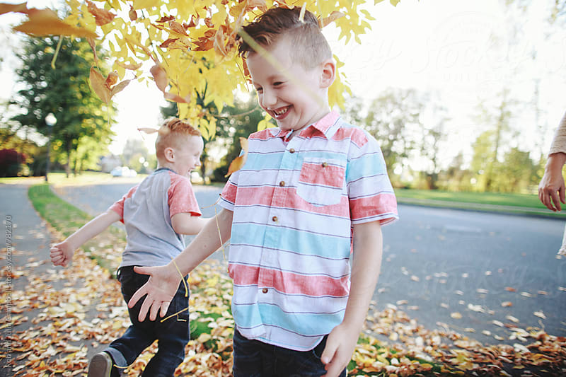 Young brothers having fun together outside in yellow leaves by Rob and Julia Campbell for Stocksy United