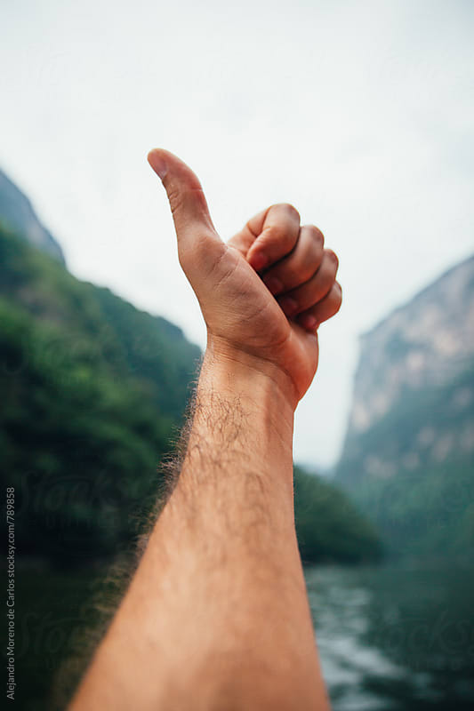 Close up of a male hand doing a thumbs up with a scenic view  of canyon and lake in Chiapas, Mexico. POV view by Alejandro Moreno de Carlos for Stocksy United