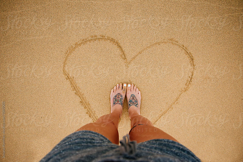 Feet woman inside a heart drawn in the sand by Susana Ramírez for Stocksy United