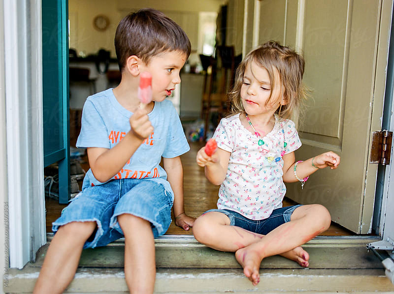 kids eating popsicle in doorway by Maria Manco for Stocksy United