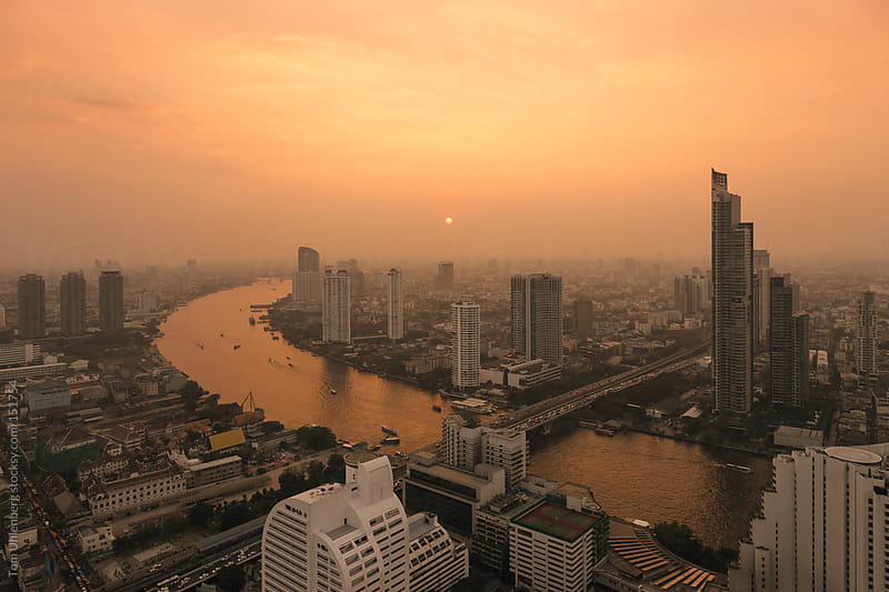 Hazy Sunset over the Chao Phraya River and the Bangkok Skyline (Thailand) by Tom Uhlenberg for Stocksy United