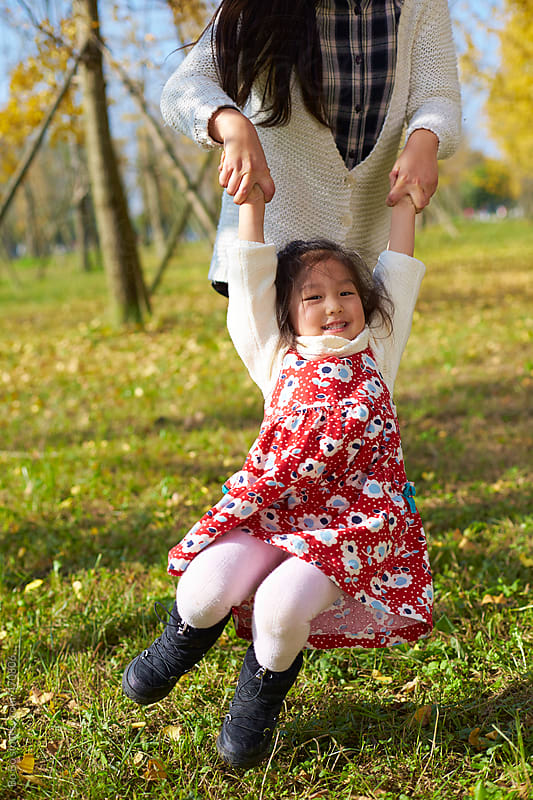 little girl playing with her mother in the park by Bo Bo for Stocksy United