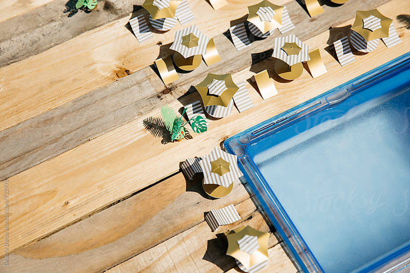 Concept of a Summer travel destination with swimming pool and paper umbrellas with tables and chairs by Beatrix Boros for Stocksy United