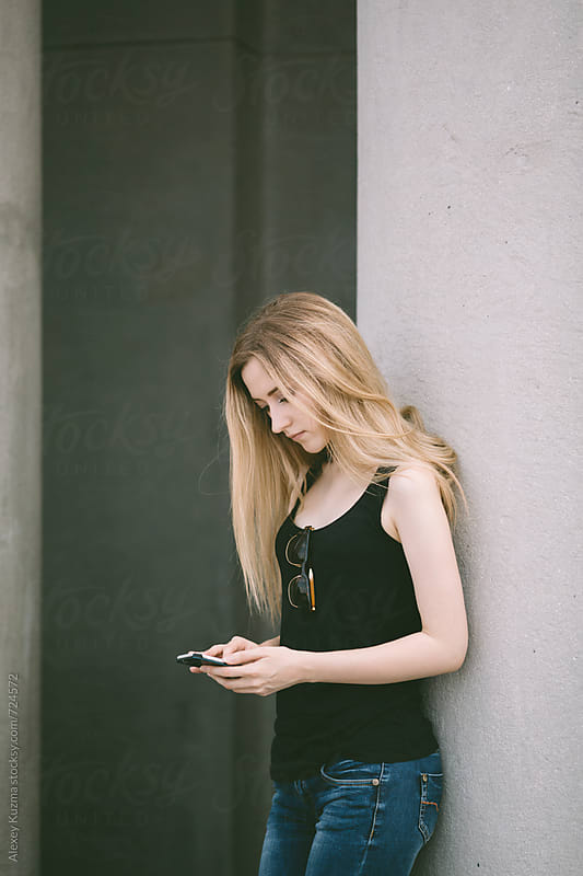 blond woman holding a cell phone outdoors by Alexey Kuzma for Stocksy United