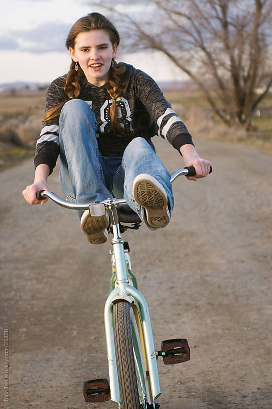 A young teen girl rides bike with feet on handle bars.  by Tana Teel for Stocksy United