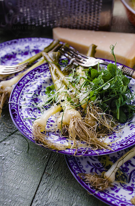 Braised baby leeks with pea shoots and parmigiano. by Darren Muir for Stocksy United