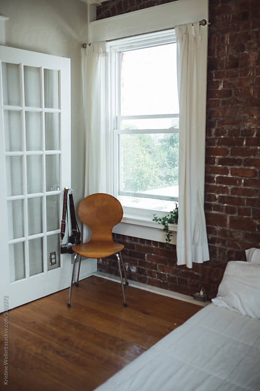A wooden chair sitting in a corner next to a window and a brick wall by Kristine Weilert for Stocksy United