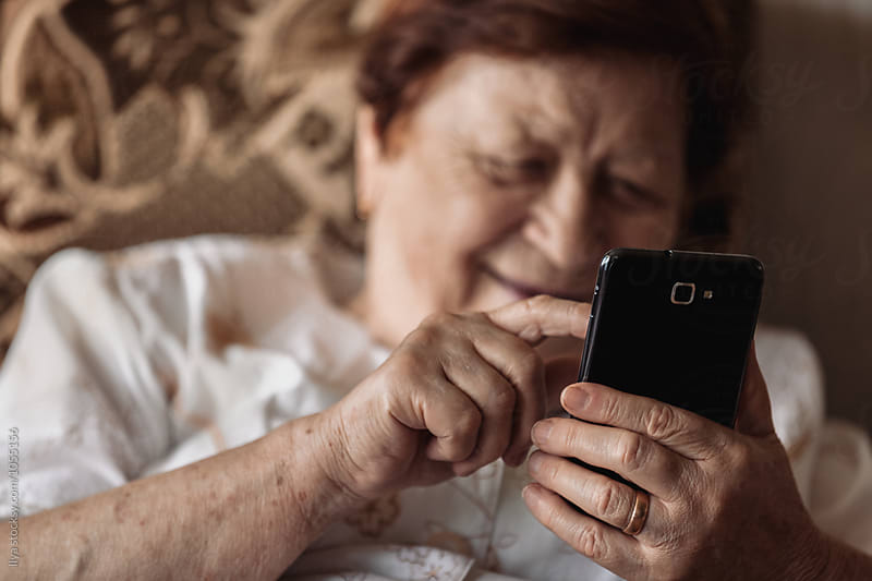 Old woman using smartphone (tablet) sitting in chair smiling by Ilya for Stocksy United