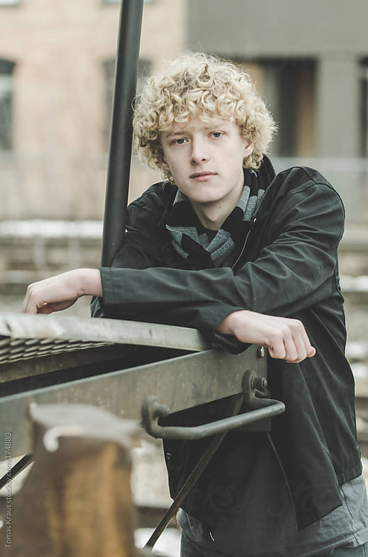 Young Man Leans Against Rail Car by Tomas Kraus for Stocksy United