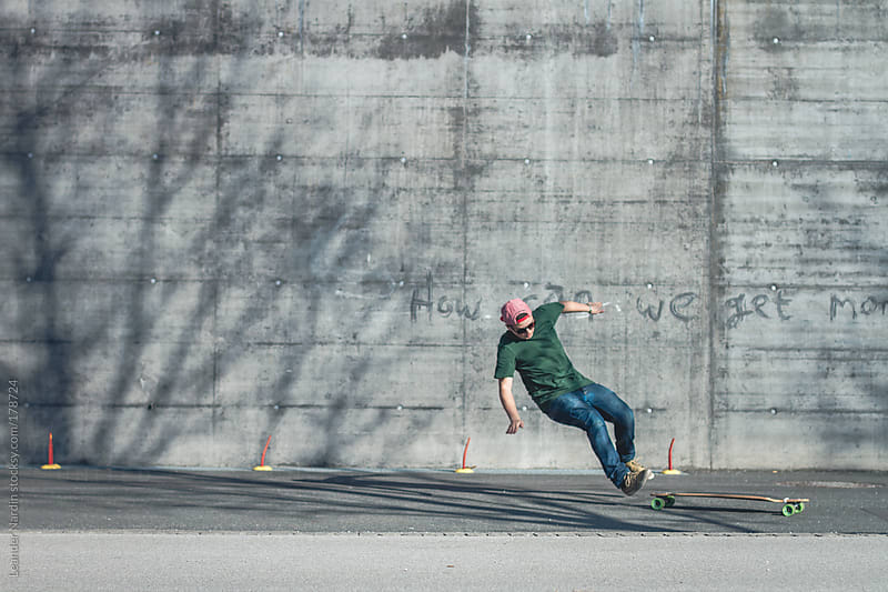 Teenager falls off his longboard in front of a wall by Leander Nardin for Stocksy United