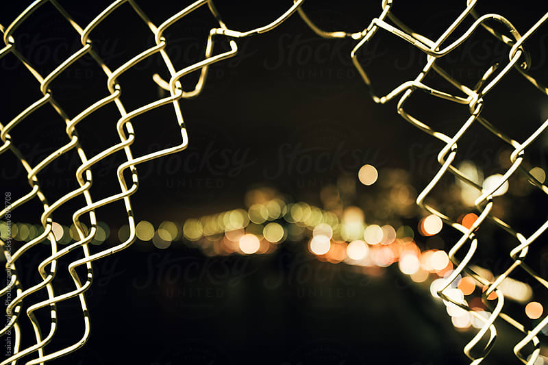Chain fence with city by Isaiah & Taylor Photography for Stocksy United