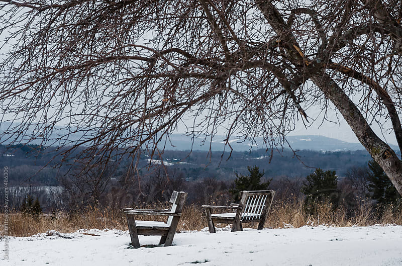 two empty benches in a snowy landscape by Deirdre Malfatto for Stocksy United