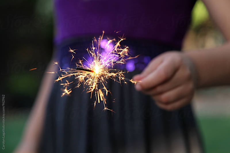 Young girl holding a sparkler by Carolyn Lagattuta for Stocksy United