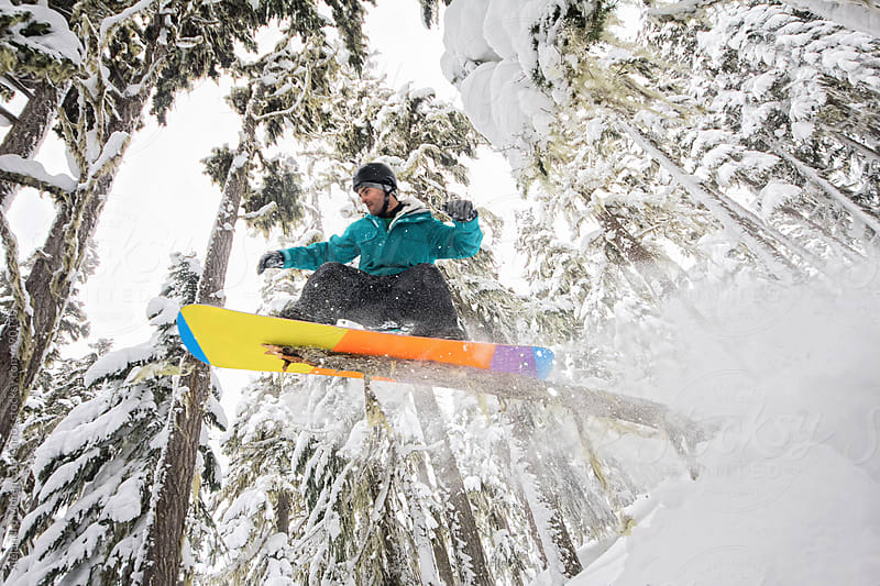 Snowboarder sliding a branch of tree with his snowboard on a powder day inside the forest on a mountain in winter by Alejandro Moreno de Carlos for Stocksy United