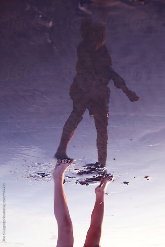 Reflection of Childs Body In Wet Ocean Sand by Dina Giangregorio for Stocksy United