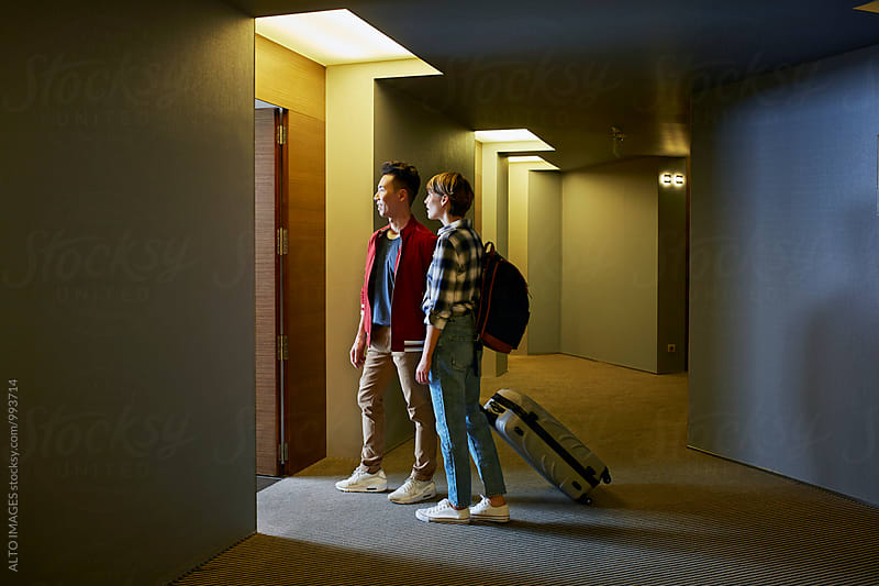 Couple Looking Into Hotel Room While Standing In Corridor by ALTO IMAGES for Stocksy United