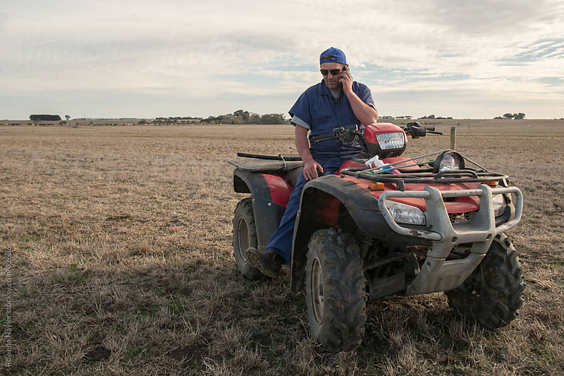 Farmer on Quad bike making a phonecall by Rowena Naylor for Stocksy United