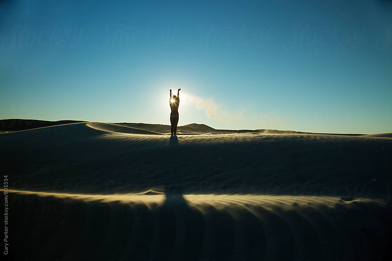 A beautiful silhouette of a naked girl in the sand dunes throwing sand into the wind by Gary Parker for Stocksy United