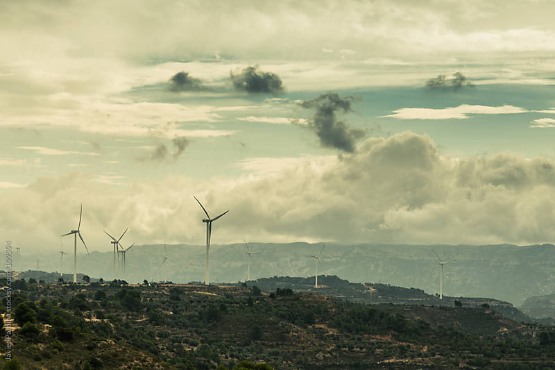 mountain landscape with windmills and a cloudy sky by Javier Pardina for Stocksy United