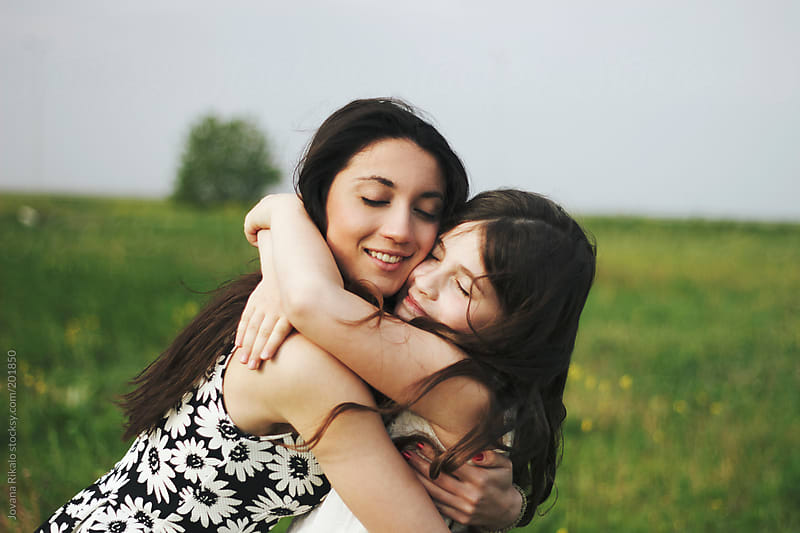 Happy sisters hugging together outdoors by Jovana Rikalo for Stocksy United