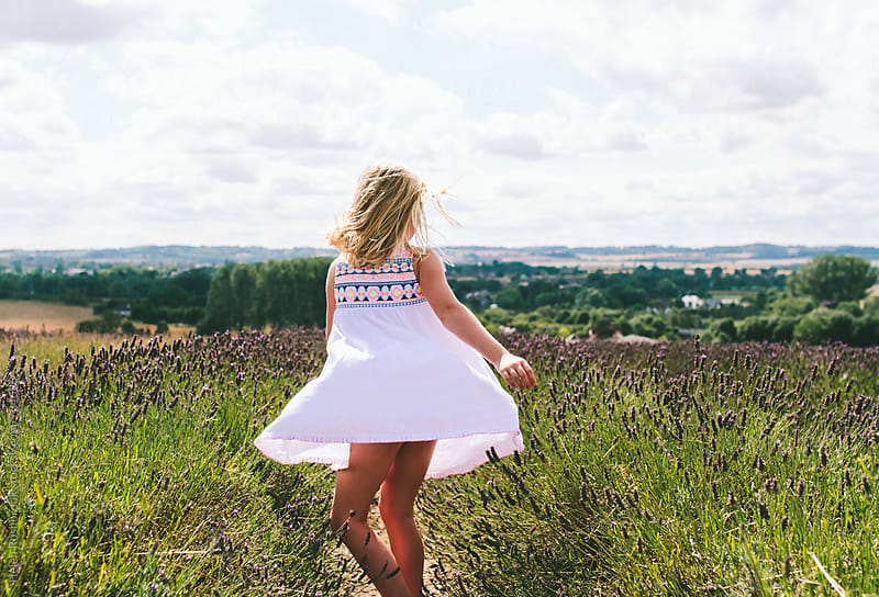 A girl dancing at the top of the hill in a lavender field by Helen Rushbrook for Stocksy United