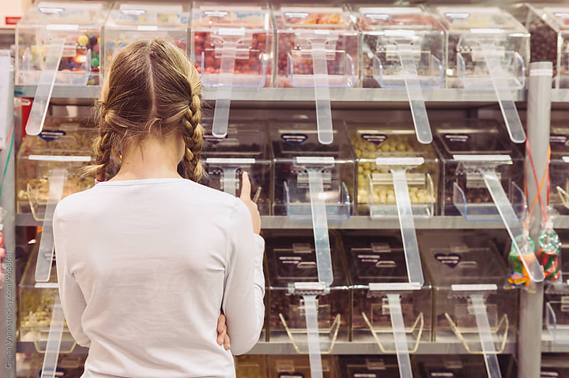 girl looking at bays of lollies in a shop by Gillian Vann for Stocksy United