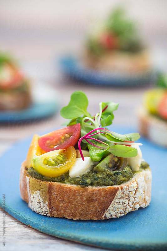 Bruschetta with Pesto and Tomatoes by Nicole S. Young for Stocksy United