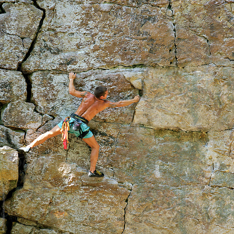 Rock climber traversing across rock face. by Hugh Sitton for Stocksy United