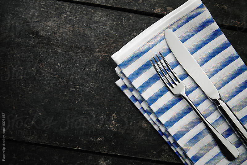 Silver cutlery and a napkin on dark wooden table by Paperclip Images for Stocksy United