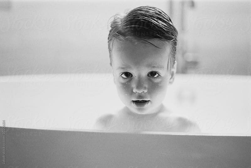 Black and white portrait of a cute young boy in a bathtub by Jakob for Stocksy United