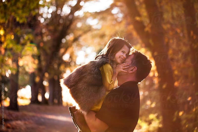 A father lifts his daughter up while playing outdoors in the fall by Amanda Worrall for Stocksy United