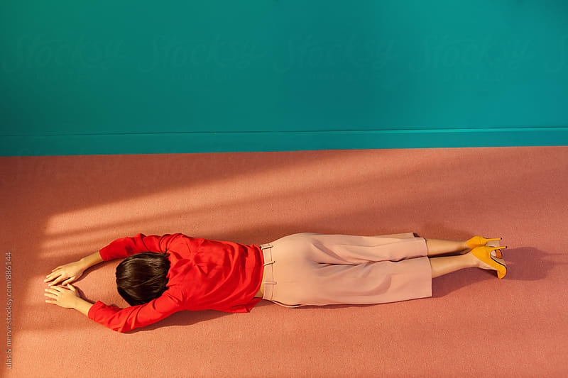 woman lying face down on the floor of a room by Ulaş and Merve for Stocksy United