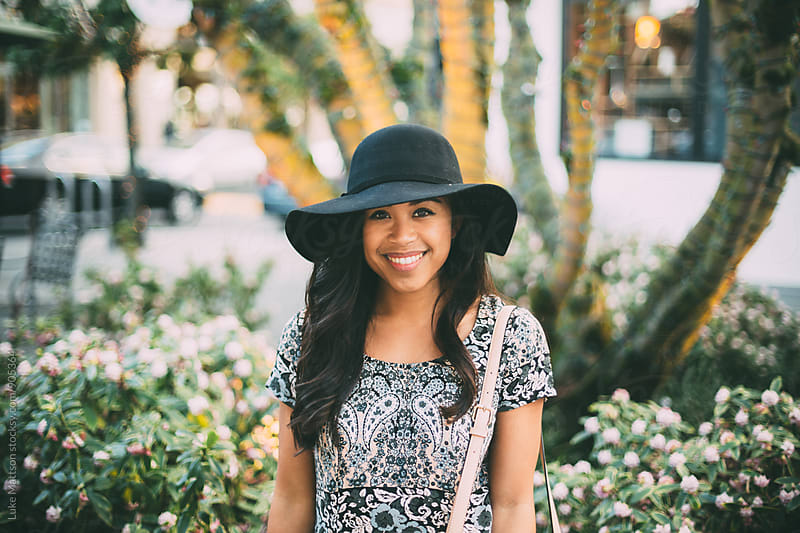 Smiling Young Woman Wearing Dress And Sun Hat by Luke Mattson for Stocksy United
