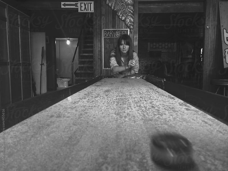 Girl, Shuffle Board, Dive Bar by Ryan Matthew Smith for Stocksy United