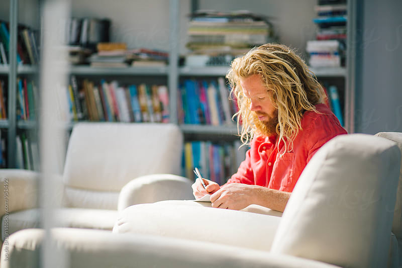 A young designer drawing or writing something down while sitting in a chair by Ivo de Bruijn for Stocksy United