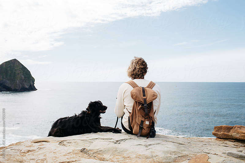 Man and dog sitting on a cliff overlooking the ocean by KATIE + JOE for Stocksy United