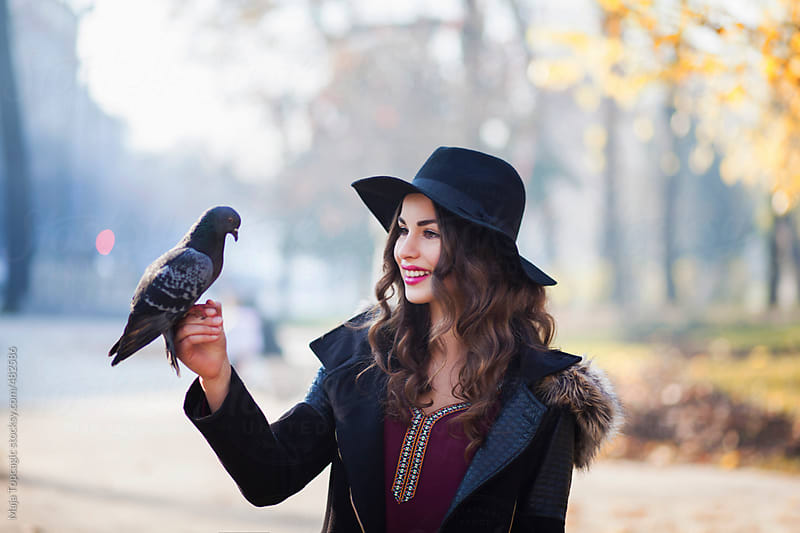 Young beautiful woman with curly hair and red lipstick on the street with a pigeon on a hand by Maja Topcagic for Stocksy United