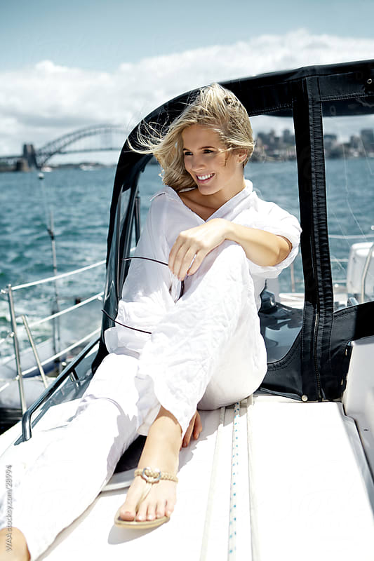 Happy young woman sitting on sail boat by WAA for Stocksy United