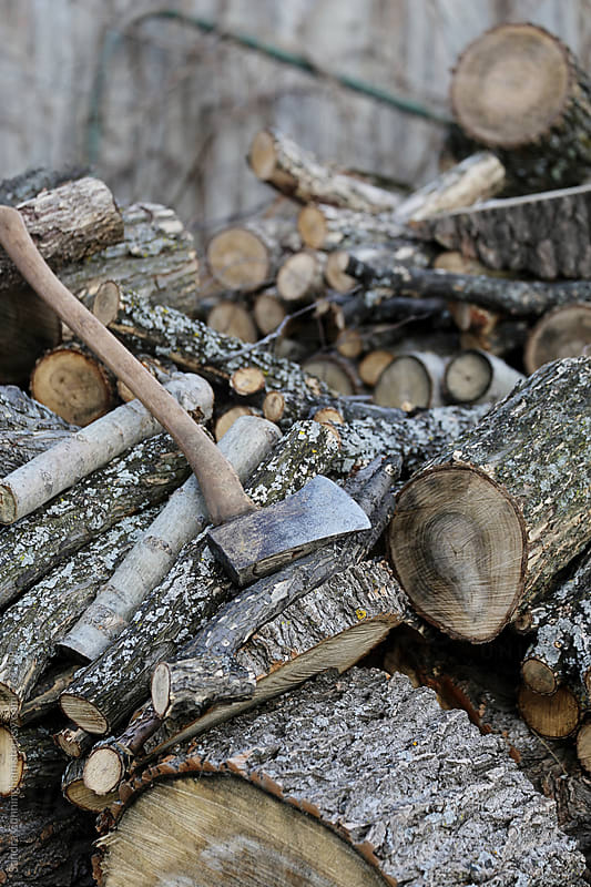 Old wood pile with axe by Sandra Cunningham for Stocksy United