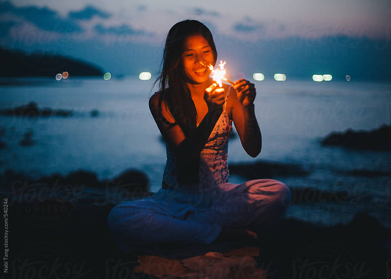 Beautiful woman by the sea with sparkler in summer night by Nabi Tang for Stocksy United
