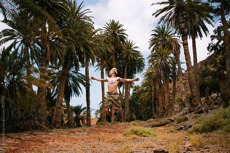 Man jumping in a palm grove by Susana Ramírez for Stocksy United