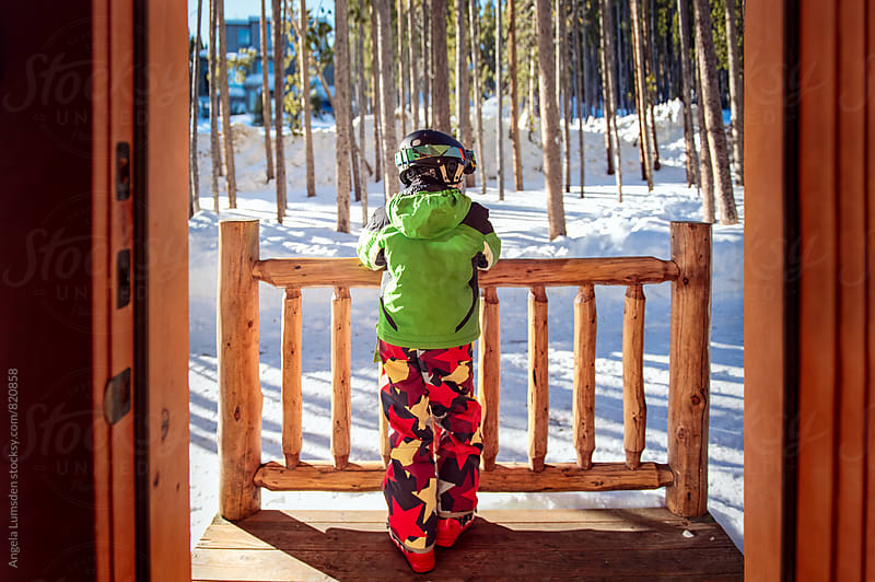 Boy dressed in ski clothes stands at the door of a ski cabin waiting to go skiing by Angela Lumsden for Stocksy United