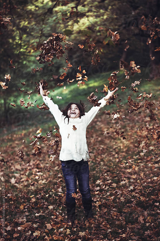 Little girl throwing autumn leaves around her by Jovana Rikalo for Stocksy United