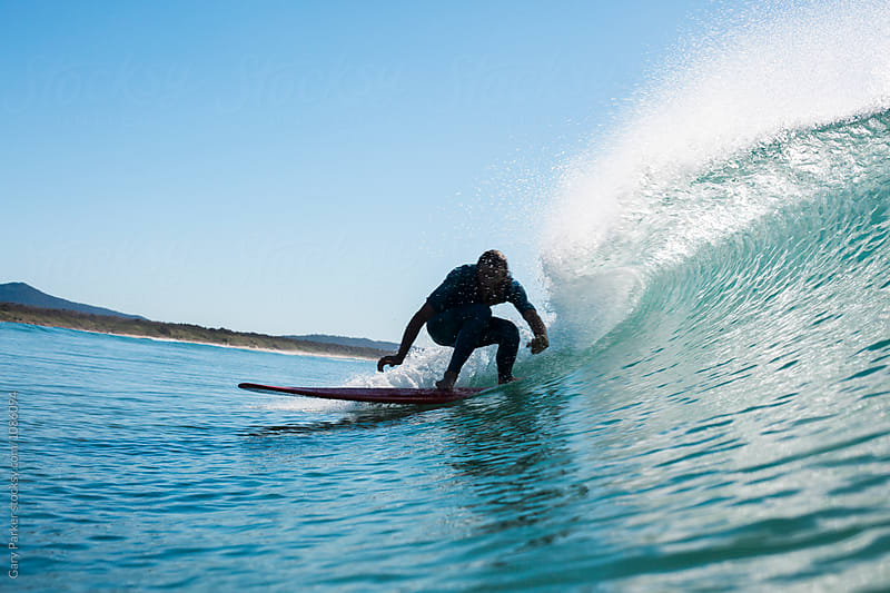 Surfer riding a small wave by Gary Parker for Stocksy United